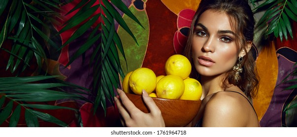 A beautiful, tanned, sexy southern beauty stands on a motley background surrounded by palm leaves and holds a wooden bowl with lemons in her hands.
