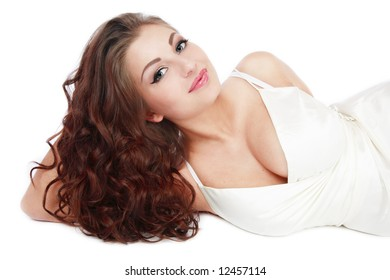 Beautiful tanned smiling girl with gorgeous curling hair lying on white background