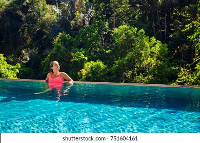 Beautiful tanned woman on summer beach holiday relaxing in luxury spa hotel in infinity swimming pool with tropical jungle view. Healthy lifestyle, family travel background.