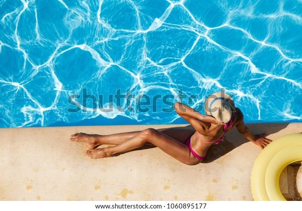 Beautiful tanned woman sitting at the poolside