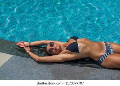 beautiful tanned young woman in bikini relaxing in swimming pool.