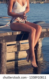 beautiful tanned young woman legs sit on wooden sea dock sunny summer day