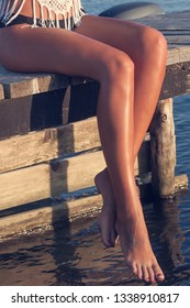 beautiful tanned young woman legs, sit on wooden sea dock sunny summer day