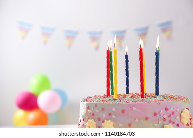 Beautiful tasty birthday cake with candles on blurred background