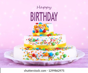 Beautiful tasty cake and phrase HAPPY BIRTHDAY on color background