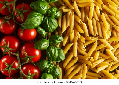 Beautiful tasty colorful pattern of italian pasta, tomatoes and basil. Top view. Abstract. Food concept.
