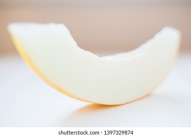 Beautiful, tasty slice of honeydew melon, isolated on white table background. Soft light on fresh slice of fruit.