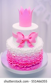 Beautiful tasty stylish two-tier pink and white cake with bow and crown. Children's cake on birthday.