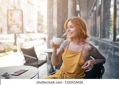 beautiful tattooed ginger girl in cafe
