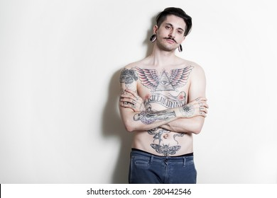beautiful tattooed man on wall.