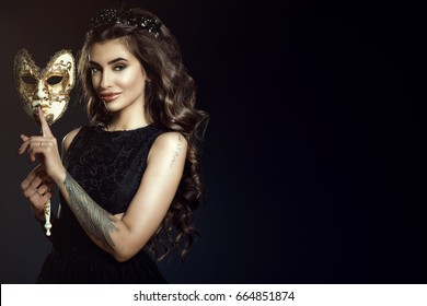 Beautiful tattooed smiling lady with dark wavy shining hair and perfect make-up wearing lace dress and jewel black crown holding a Venetian mask in her hand with silence gesture. Copy space