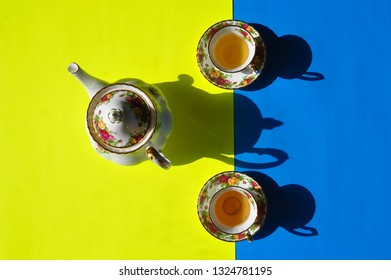 Beautiful tea cups and a tea pot in a asymmetrical yellow and blue backgrounds with shadow