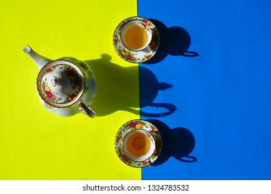 Beautiful tea cups and a tea pot in a yellow and blue backgrounds with shadow in the morning