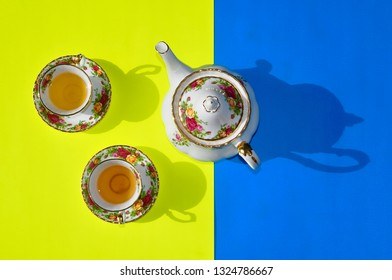 Beautiful tea cups and a tea pot in a yellow and blue backgrounds with shadow