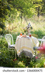 Beautiful tea setting in green garden in armudu cup with samovar, bread, rose jam on round table with bouquet of flowers and white chairs, fresh hot drink, summer green background
