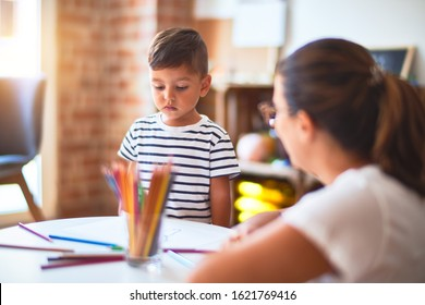 Beautiful teacher and toddler boy drawing draw using colored pencils at kindergarten - Shutterstock ID 1621769416