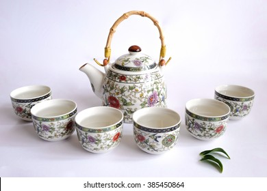 beautiful teapot and teacups on white background