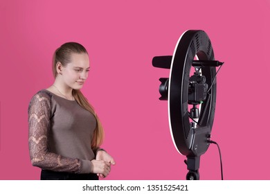 The beautiful teen blogger have posing on camera with ring light. In the studio on a pink background.