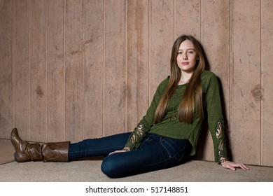 Beautiful teen girl in green sweater seated and leaning on a wall