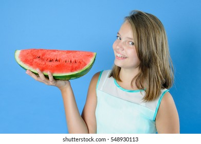Beautiful teen girl holding in one hand a large piece of ripe watermelon. Studio photography on a light blue background.
