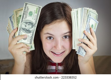 Beautiful teen girl holding US dollars. Happy face expression