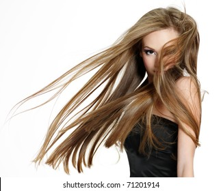 Beautiful teen girl shaking head with long hair on white background