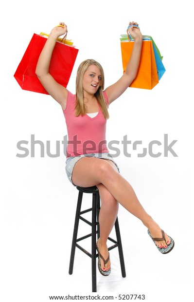 Beautiful teen girl shopping and smiling isolated on a white background