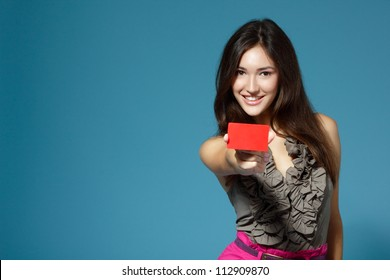 beautiful teen girl showing red card in hand, over blue background
