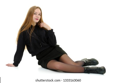 A beautiful teen girl sits on the floor on a white background. The concept of education and schoo. Isolated.