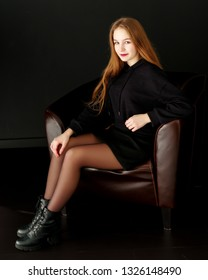Beautiful teen girl sits in the studio on a leather chair. Concept of youth fashion and culture.On a black background.