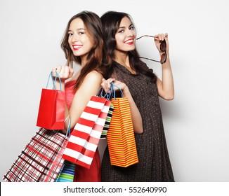 Beautiful  teen girls carrying shopping bags, over white backgro