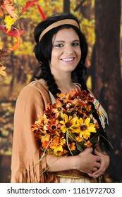 """A beautiful teen """"Indian Maiden"""" happily carrying a large bouquet of fall flowers.  She's in a colorful forrest setting."""
