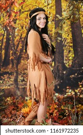 A beautiful teen Indian maiden looking back at the viewer as she walks in a colorful autumn woods.
