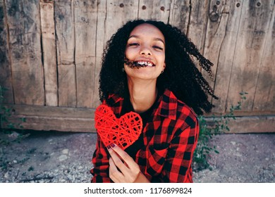 Beautiful teen woman holding a red heart