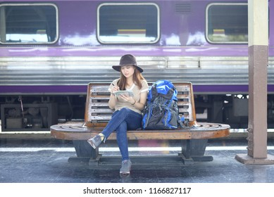 Beautiful teenage Asian woman tourist is solo traveling and looking at the map in the Bangkok train station.