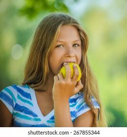 Beautiful teenage girl biting an apple, against green of summer park.