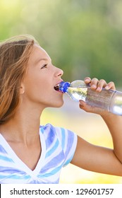 Beautiful teenage girl in blue blouse drinks water from bottle, against green of summer park.