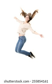 Beautiful teenage girl with broad happy smile jumping with joy, dancing, wearing jeans, jersey and knitted hat, isolated