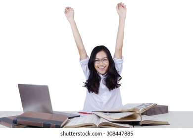 Beautiful teenage girl celebrate back to school while raising hands and studying with books and laptop, isolated on white