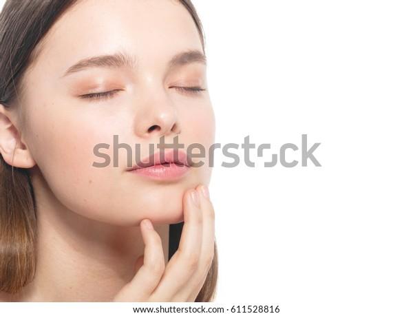 白い背景に美しい10代の女の子の目を閉じた美しい顔と健康そうな肌のポートレート