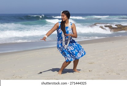 A beautiful teenage girl dancing hula on an empty beach.  She is wearing a traditional hula dance outfit, a long shell necklace and a plumeria flower in her hand.