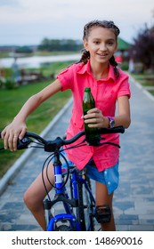 beautiful teenage girl drinks water after a bike ride