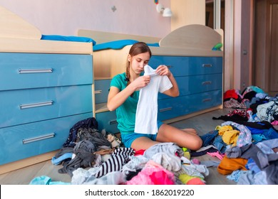 Beautiful teenage girl folding her clothes in a messy bedroom