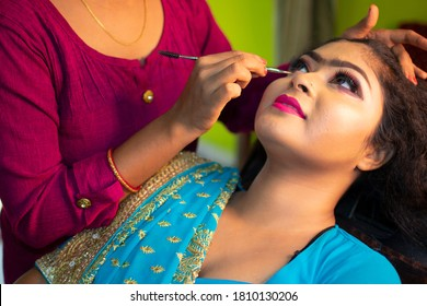 A beautiful teenage girl getting traditional face makeup at a beauty parlour