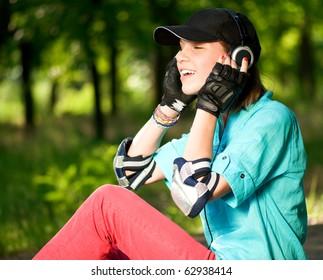 Beautiful teenage girl with headphones in the green park