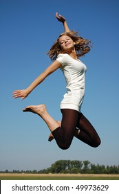 Beautiful teenage girl jumping on a meadow smiling cheerfully