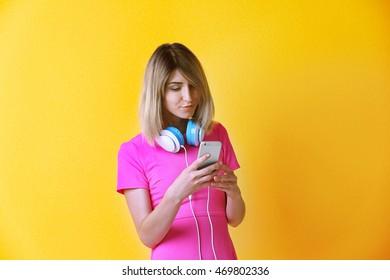Beautiful teenage girl listening music on yellow background