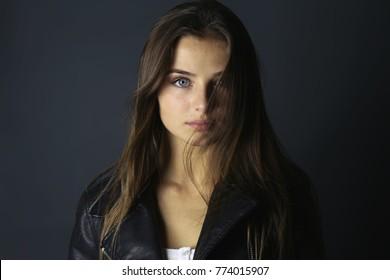 Beautiful teenage girl looking at camera . Fashion girl wearing a black leather jacket on studio
