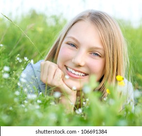 Beautiful Teenage Girl lying on Meadow of Flowers and Green Grass.. Happy and Smiling.