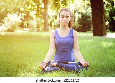 beautiful teenage girl meditates in nature